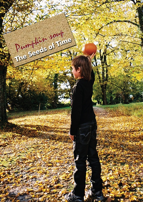 Poster art for album titled Pumpkin Soup by The Seeds of Time on which there is a photograph of a boy holding a pumpkin above his head while standing in a forest surrounded by an autumn scene and yellow leaves